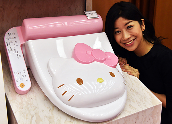 An employee for Japanese character goods maker Sanrio displays a prototype model of a Hello Kitty branded toilet seat at Sanrio's headquarters in Tokyo on February 2, 2015. The toilet seat has seat heating and warm water shower functions. AFP PHOTO / Yoshikazu TSUNO (Photo credit should read YOSHIKAZU TSUNO/AFP/Getty Images)